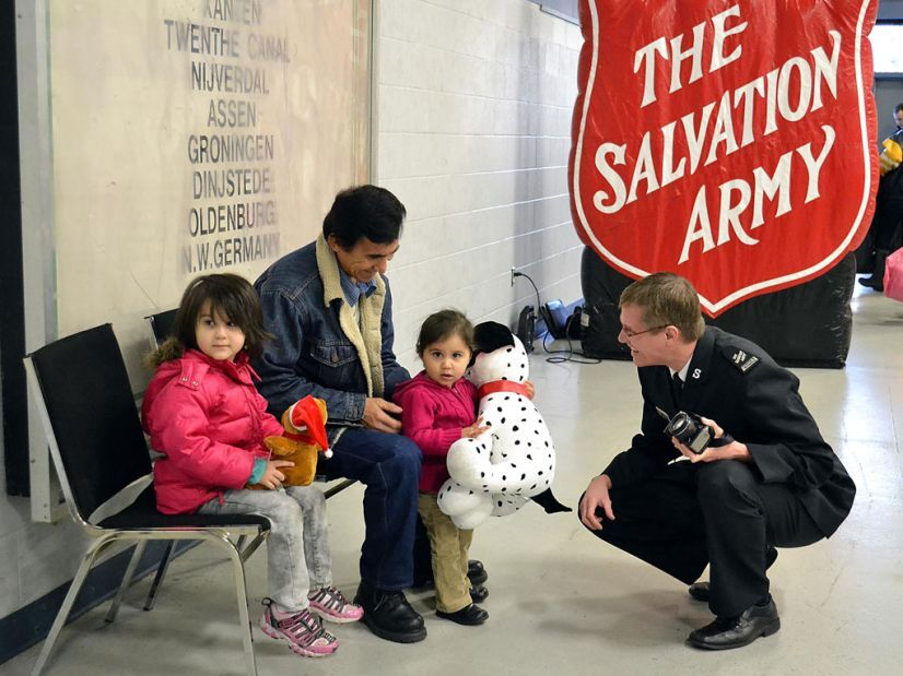 Salvation Army worker chatting with children